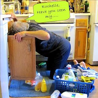Errol on knees looking for something under sink