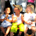 three littke kids eating ice cream cones with blissful look on their faced looking up eyes closed